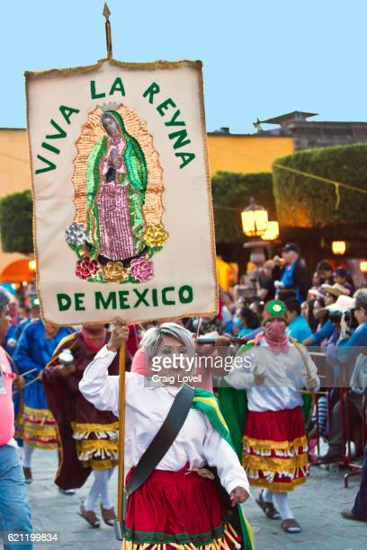 A Mexican dwoman carries Virgin de Guadalupe banner during a parade celebrating the anniversary of the city - SAN MIGUEL DE ALLENDE, MEXICO