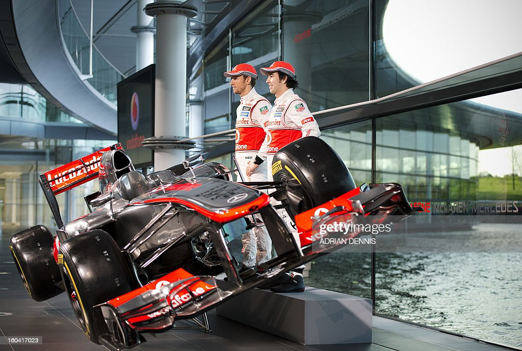 Mexican F1 driver Sergio Checo Perez (R) and British F1 driver Jenson Button pose for pictures as the new McLaren Mercedes MP4-28 F1 racing car for the 2013 season is unveiled at the McLaren Technology Centre in Woking, southern England, on January 31, 2013. Mexican driver Sergio Checo Perez joins Britain's Jenson Button for the 2013 season following the departure of Britain's Lewis Hamilton.