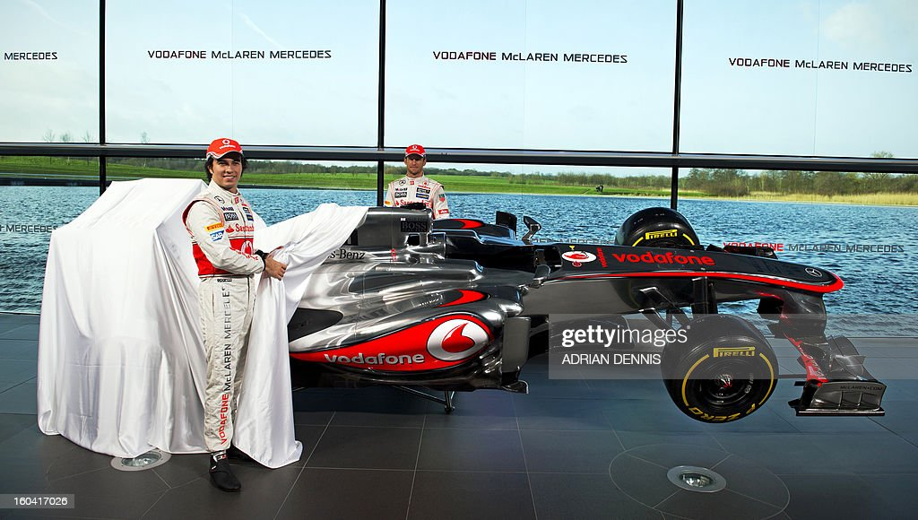 Mexican F1 driver Sergio Checo Perez (Foreground) and British F1 driver Jenson Button pose for pictures as the new McLaren Mercedes MP4-28 F1 racing car for the 2013 season is unveiled at the McLaren Technology Centre in Woking, southern England, on January 31, 2013. Mexican driver Sergio Checo Perez joins Britain's Jenson Button for the 2013 season following the departure of Britain's Lewis Hamilton.