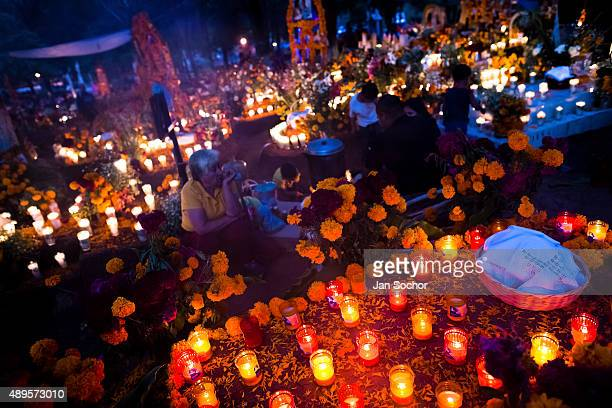 Mexican family members light candles and pray at the cemetery to honor their deceased relatives during the Day of the Dead celebration on November 02...