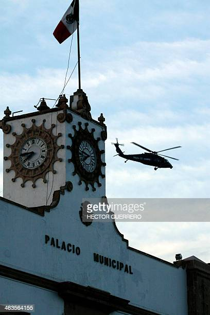 A Mexican federal police helicopter flies over Apatzingan Michoacan State Mexico on January 18 2014 Federal forces in recent days have moved into...