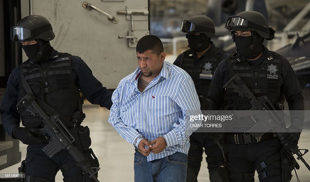 Mexican Federal police personnel escort David Rosales Guzman, aka 'Commander Devil', alleged member of the Gulf cartel, during his presentation to the press at the Police Command Centre in Mexico City on September 02, 2012. According to the Mexican authorities , Rosales Guzman was in charge of the illegal drug trafficking In Monterrey, north Mexico.