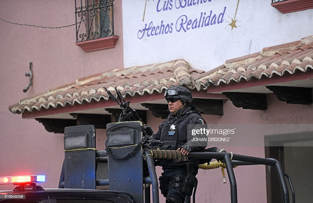 Mexican Federal Police personnel keeps watch ona vehicle in a checkpoint at the entrance of the village of Zinacantan, in the surroundings of the place where Pope Francis will officiate an open-air mass, Chiapas State, Mexico on February 13, 2016. Pope Francis urged Mexican bishops Saturday to take on drug trafficking with 'prophetic courage,' warning that it represents a moral challenge to society and the church. AFP PHOTO/Johan ORDONEZ / AFP / JOHAN ORDONEZ