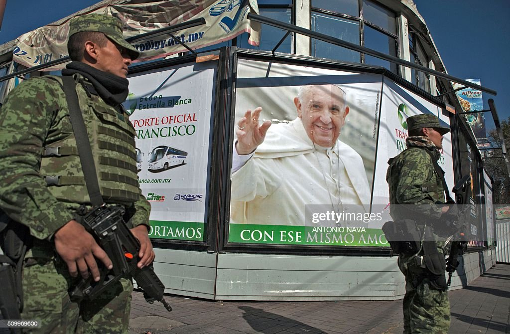 Mexican federal policemen stand guard as Pope Francis heads to the National Palace, in Mexico City on February 13, 2016. Francis became the first pope to enter Mexico's National Palace to meet President Enrique Pena Nieto, as he starts a cross-country tour that will highlight the country's violence and migration troubles. AFP PHOTO / ANTONIO NAVA / AFP / ANTONIO NAVA