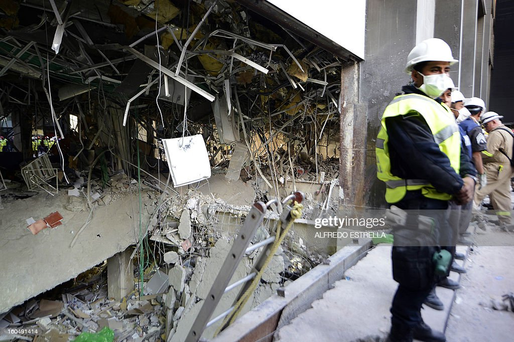 Mexican Federal policemen stand guardnext to the damaged building of state-owned Mexican oil giant Pemex, following a blast on the eve, in Mexico City on February 1, 2013. An explosion rocked the skyscraper, leaving up to 32 dead and 121 injured. Hundreds of firefighters, police and soldiers toiled through the night after the blast ripped through an annex of the 54-floor tower leaving concrete, computers and office furniture strewn on the ground. AFP PHOTO/Alredo Estrella