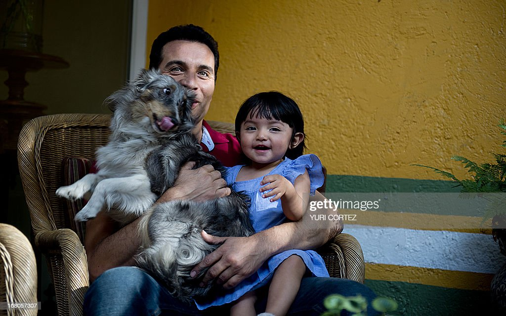 Mexican Felipe Najera, a gay soap opera actor, remains in the garden of his house with his adopted daughter and their pet on April 29, 2013 in Mexico City. After their marriage, Najera and Jaime Morales -a theatre producer- became the first gay couple to which the Mexican State committed a minor for adoption. AFP PHOTO/ Yuri CORTEZ