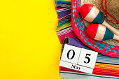 Mexican fiesta poster and Cinco de Mayo party concept theme with calendar on may 5th, red and blue maracas, sombrero and traditional rug on yellow background with copy space