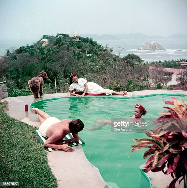 Mexican film star Dolores Del Rio lounges by the pool with Micki Salle a friend and a poodle Acapulco 1952