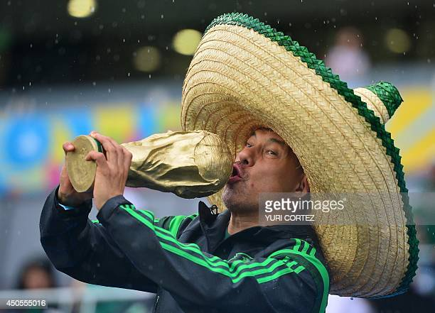 A Mexican football fan kisses a replica of the FIFA World Cup trophy before the start of a Group A football match between Mexico and Cameroon at the...