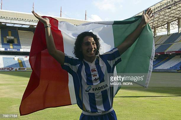 Mexican football player Andres Guardado salutes to fans with a flag of Mexico during his presentation ceremony as new Deportivo Coruna's player at...