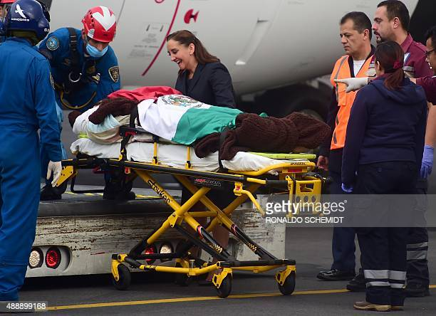 Mexican Foreign Minister Claudia Ruiz Massieu talks with one the six Mexican tourists wounded in a military attack in Egypt upon deplaning from the...