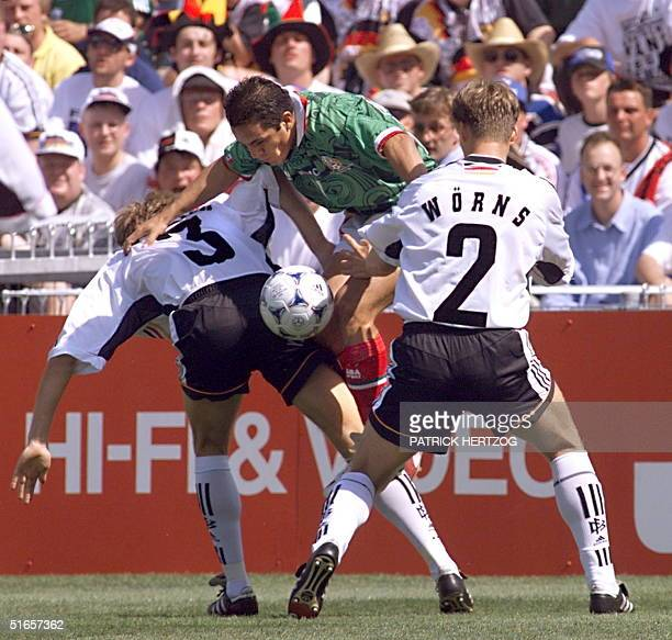 Mexican forward Cuauhtemoc Blanco jumps between German Jorg Heinrich and Christian Woerns 29 June at the Stade de la Mosson in Montpellier south of...