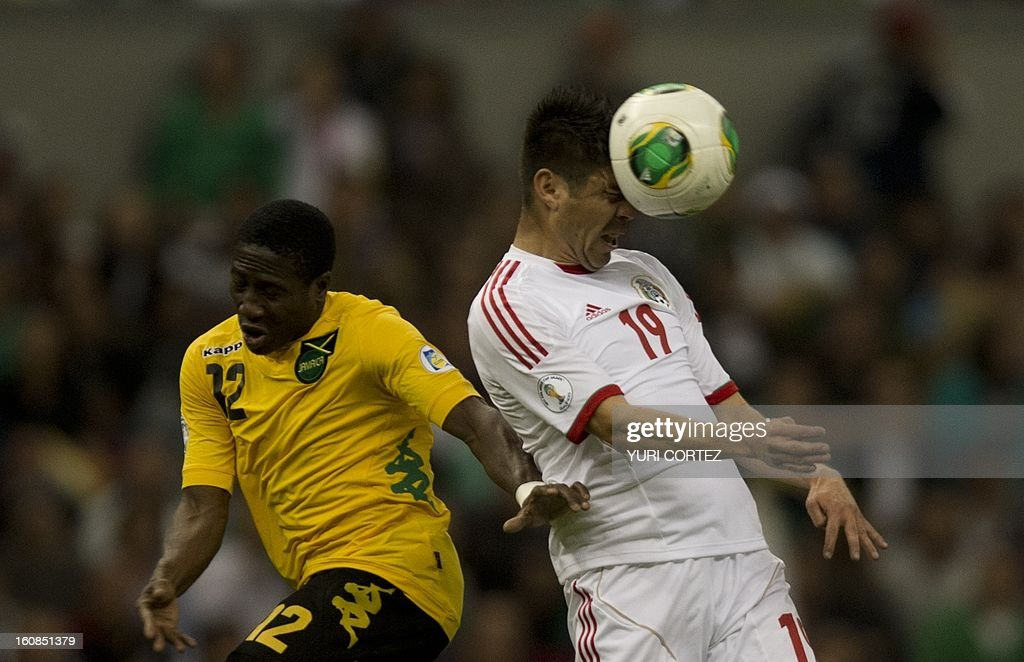 Mexican forward Oribe Peralta (R) heads the ball with Jamaica's Demar Phillips (L) during their their Brazil-2014 FIFA World Cup CONCACAF football qualifier match at the Azteca stadium in Mexico City, on February 6, 2013.