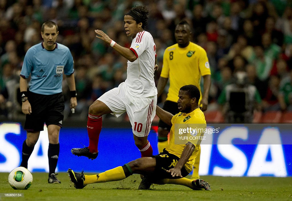 Mexican Giovani Dos Santos (C) disputes the ball with Jamaica's Jermaine Taylor (R) during their their Brazil-2014 FIFA World Cup CONCACAF football qualifier match at the Azteca stadium in Mexico City, on February 6, 2013.