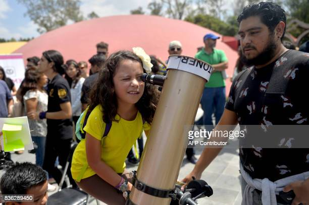 A Mexican girl looks through a telescope at the beginning of the solar eclipse at the esplanade of the Museum of Natural History in Mexico City on...