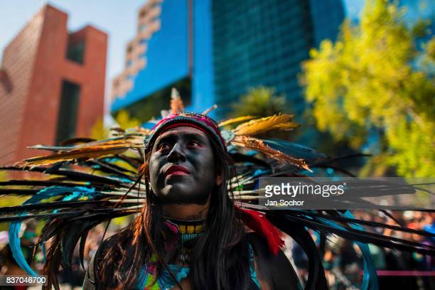 Mexican girl wearing a colorful feather headgear inspired by Aztecs looks on during the Day of the Dead celebrations in Mexico City Mexico October 29...