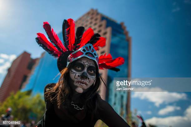 Mexican girl wearing a feather headgear inspired by Aztecs dances on the street during the Day of the Dead procession on October 29 2016 in Mexico...