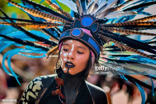 Mexican girl wearing a large feather headgear inspired by Aztecs looks on during the Day of the Dead celebrations on October 29 2016 in Mexico City...