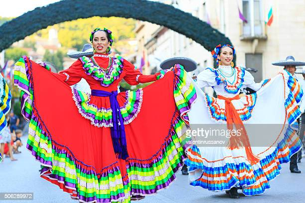 Mexican girls in traditional costumes dancing at festival