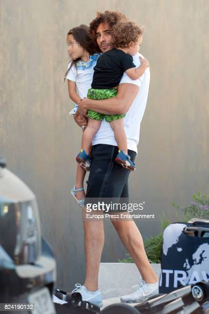 Part of this image has been pixellated to obscure the identity of the child Mexican goalkeeper Guillermo Ochoa is seen arriving to Ibiza before his...