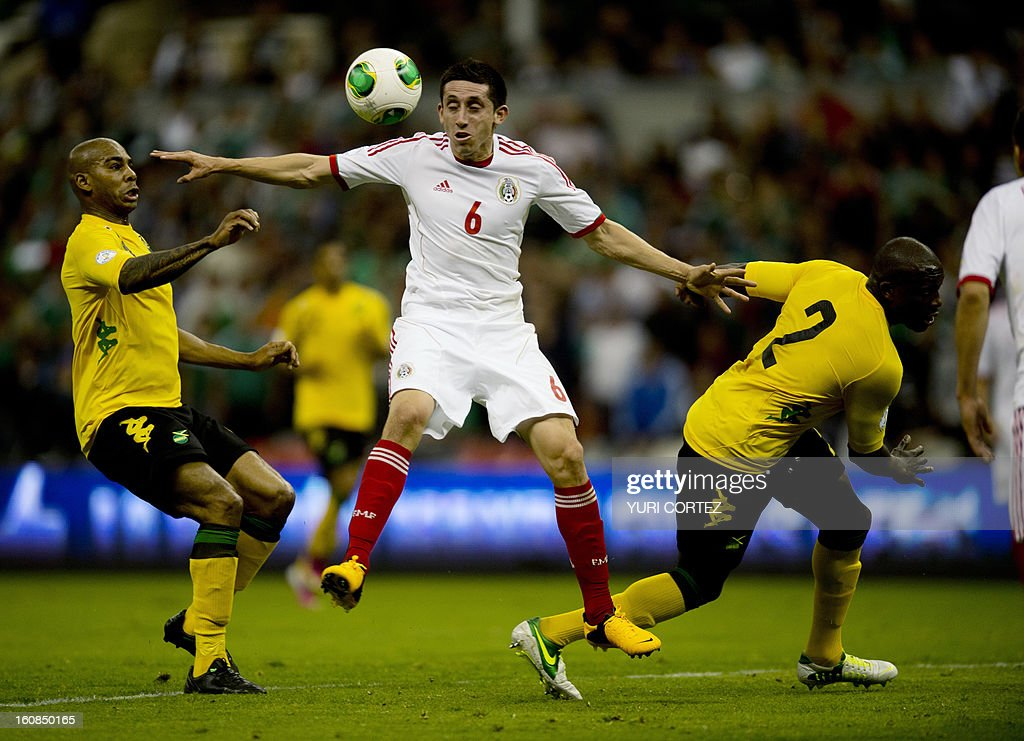 Mexican Hector Herrera (C) vies for the ball with Jamaica's Marvin Elliott (L) during their their Brazil-2014 FIFA World Cup CONCACAF football qualifier match at the Azteca stadium in Mexico City, on February 6, 2013.