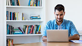Mexican hipster man working with computer indoor at desk at home
