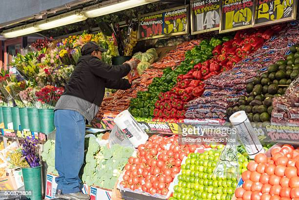 Mexican immigrant working arranging fruit in a convenience store in New York city Beautifully arranged display of fruits and other produce wiht...