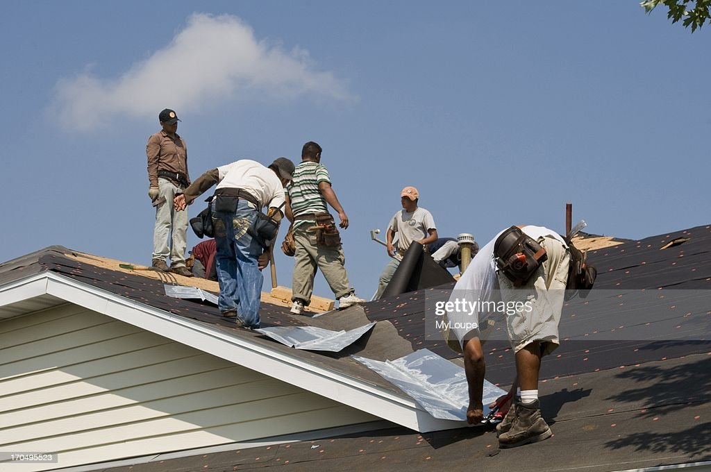 & Replacing a roof on a building. Pictures | Getty Images memphite.com