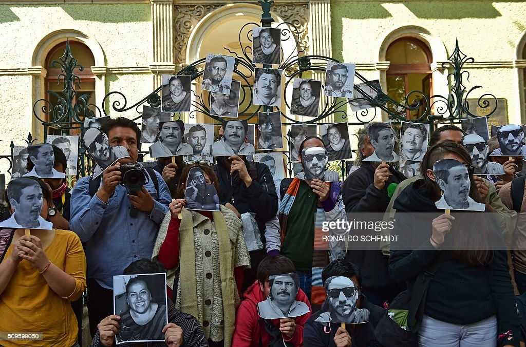 Mexican journalists pose with photos of killed journalists outside the Veracruz state representation office during a protest in Mexico City on February 11, 2016. Mexican journalist Anabel Flores Salazar's funeral took place Wednesday after she was found killed at a road after being kidnapped Monday in Veracruz state, one of the most dangerous for journalists. AFP PHOTO/RONALDO SCHEMIDT / AFP / RONALDO SCHEMIDT