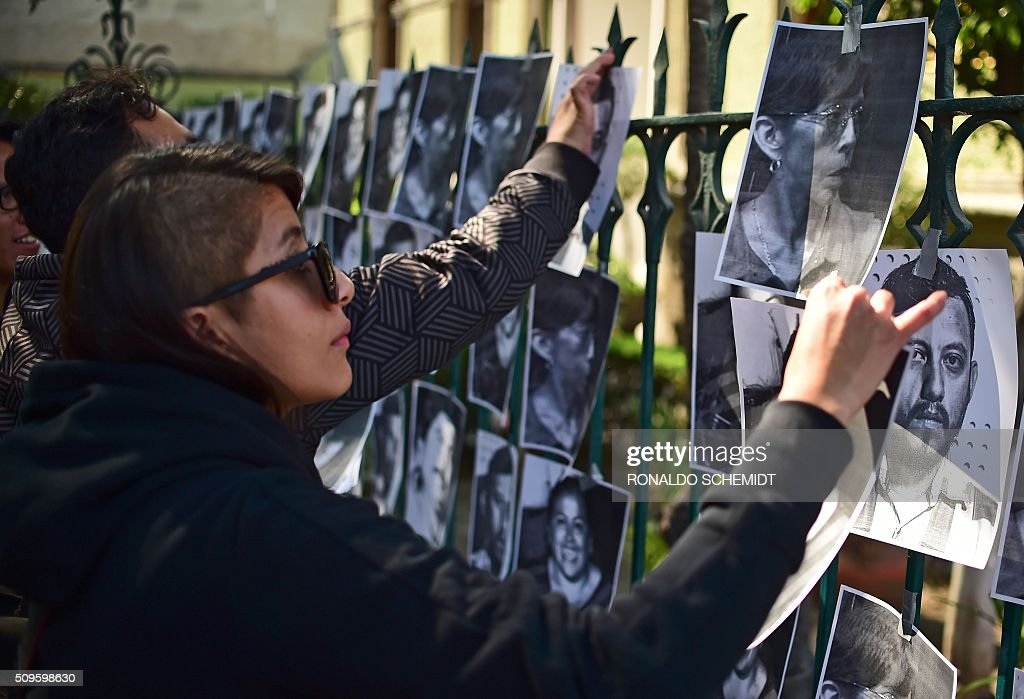 Mexican journalists stick photos of killed journalists on the fence of the Veracruz state representation office during a protest in Mexico City on February 11, 2016. Mexican journalist Anabel Flores Salazar's funeral took place Wednesday after she was found killed at a road after being kidnapped Monday in Veracruz state, one of the most dangerous for journalists. AFP PHOTO/RONALDO SCHEMIDT / AFP / RONALDO SCHEMIDT