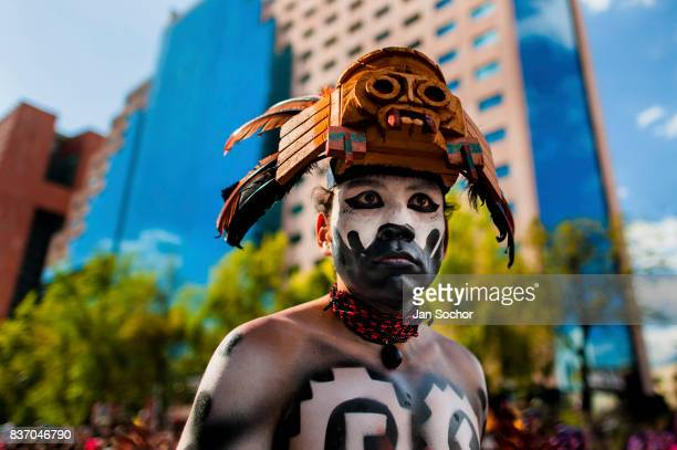 Mexican man wearing a colorful feather mask inspired by Aztecs looks on during the Day of the Dead parade on October 29 2016 in Mexico City Mexico...