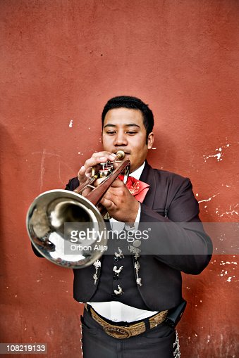 Mexican Mariachi Man Playing Trumpet Against Wall