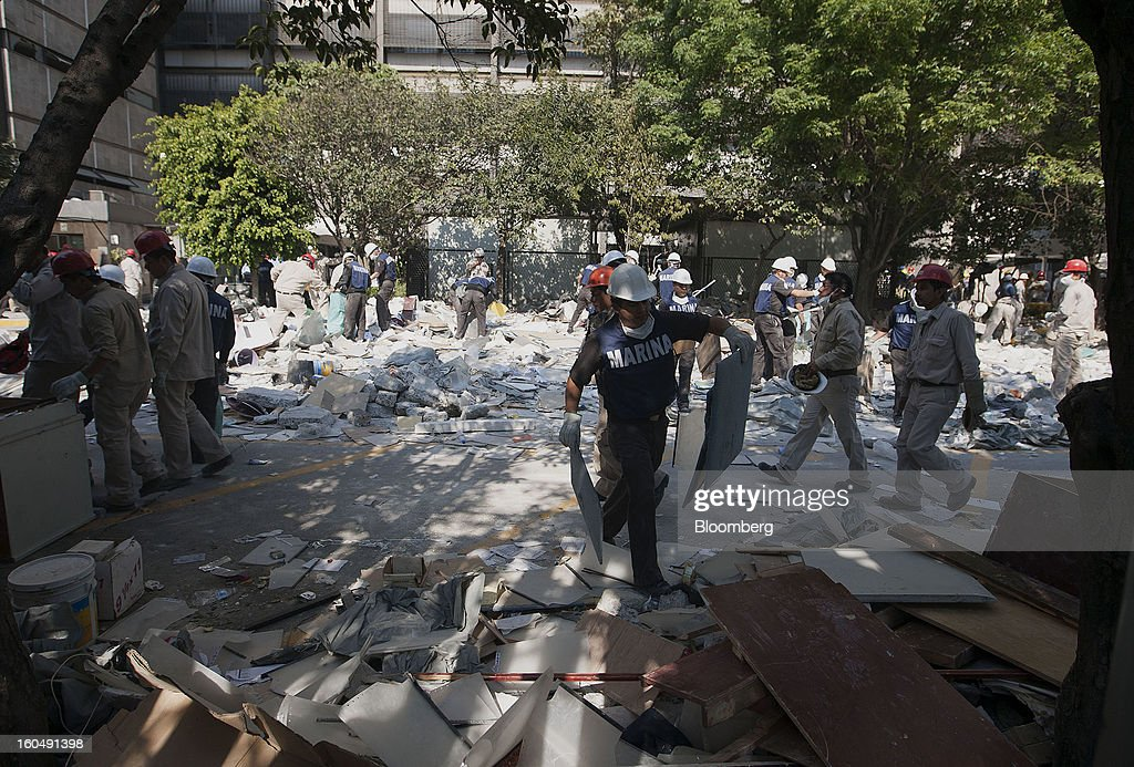 A Mexican marine tosses debris at the Petroleos Mexicanos (Pemex) administrative building in Mexico City, Mexico, on Friday, Feb. 1, 2013. Pemex is stepping up security at oil production facilities as authorities investigate a blast that killed at least 33 people at the state-owned company's headquarters in Mexico City yesterday. Photographer: Susana Gonzalez/Bloomberg via Getty Images