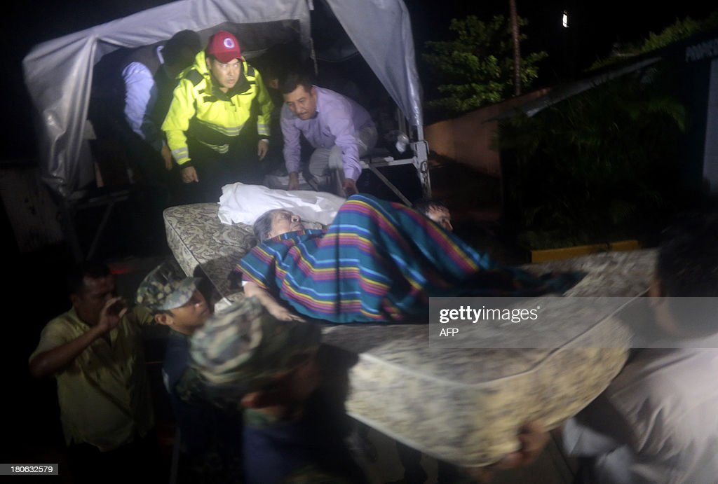 Mexican marines carry an elderly woman to a shelter after her home was flooded by rains caused by tropical storm Manuel in Acapulco, Guerrero state, Mexico on September 15, 2013. At least nine people died in the state of Guerrero due to the heavy rains caused by tropical storm Manuel, near the Pacific coast, while in the eastern state of Veracruz 6,000 had to be evacuated due to hurricane Ingrid, local authorities said. AFP PHOTO/ Pedro PARDO