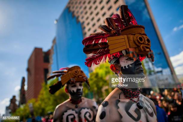 Mexican men wearing colorful feather masks inspired by Aztecs walk through the street during the Day of the Dead festival on October 29 2016 in...