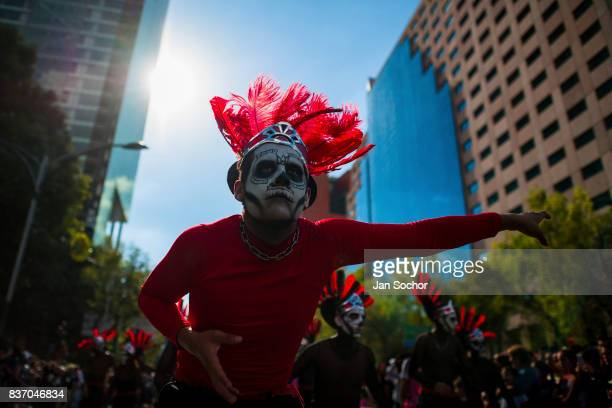 Mexican men wearing feather headgears inspired by Aztecs dance in the street during the Day of the Dead festival on October 29 2016 in Mexico City...