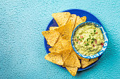 Mexican nachos, tortilla chips with guacamole sauce over blue background, top view