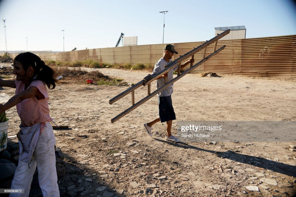 A Mexican National carries a ladder in order to view the border wall prototypes under construction looking from Mexico on October 5, 2017 in Tijuana, Mexico. Prototypes of the border wall propopsed by President Donald Trump are being built just north of the U.S.- Mexico border, where competitors who are hoping to gain approval to build the wall have until the first of next month to complete their work.