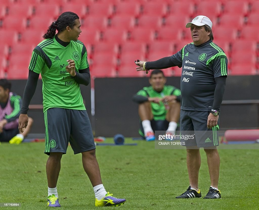 Mexican national football team coach Miguel Herrera (R) talks to player Carlos Pena during a training session on November 12, 2013 in Mexico City. Mexico will face New Zealand in Mexico City next November 13 in a playoff qualifier match for the FIFA World Cup Brazil 2014.