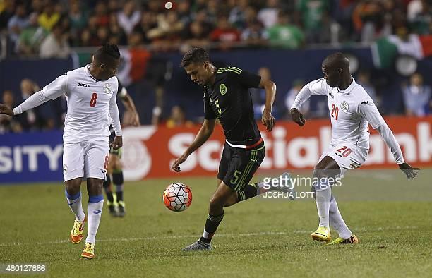 Mexican National Team defender Diego Reyes controls the ball between Cuban National Team midfielder Alberto Gomez and forward Armando Coroneaux...