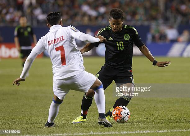 Mexican National Team forward Giovani Dos Santos fights for the ball with Cuban National Team midfielder Dario Suarez during the second half of their...