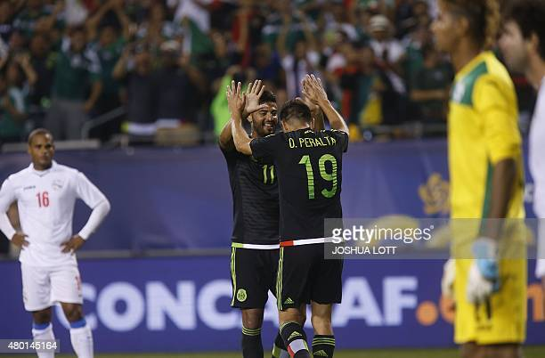 Mexican National Team forward Oribe Peralta celebrates his goal with teammate Carlos Vela as Cuban National Team players look on during the second...