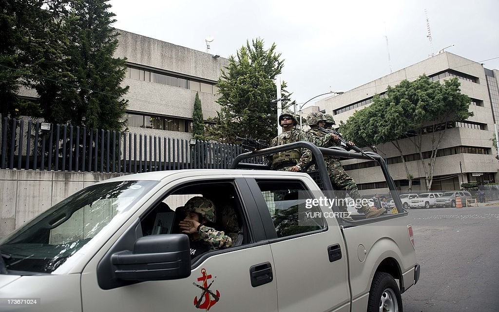 Mexican Navy marines patrol in a truck the surroundings of the Deputy Attorney Specialized in Investigation of Organized Crime (SEIDO) headquarters, where the alleged maximun leader of drugs Mexican cartel 'Los Zetas' Miguel Angel Trevino Morales, aka 'Z 40', remains under investigation, in Mexico City on July 16, 2013. Trevino's arrest early Monday by Mexican Navy near Nuevo Laredo (Tamaulipas, northeast), bordering the United States, is the most significant blow against drug trafficking by Enrique Pena Nieto government who took office last December. AFP PHOTO / Yuri CORTEZ