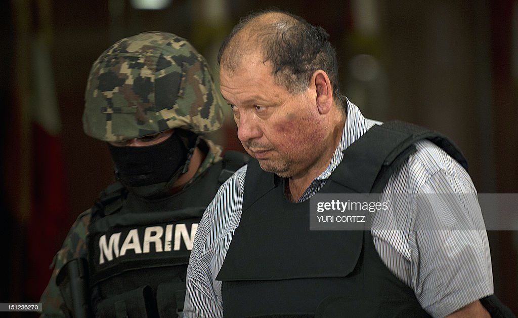 A Mexican Navy member escortsMario Cardenas Guillen, aka 'El M-1' and alleged leader of the Gulf drug cartel, during his presentation to the press in Mexico City on September 4, 2012. According to the Navy's spokeman, Cardenas was arrested during a military operation in Altamira, Tamaulipas on September 3.