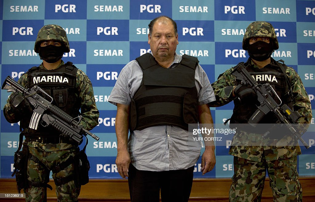 Mexican Navy members escort Mario Cardenas Guillen (C), aka 'El M-1' and alleged leader of the Gulf drug cartel, during his presentation to the press in Mexico City on September 4, 2012. According to the Navy's spokesman, Cardenas was arrested during a military operation in Altamira, Tamaulipas on September 3. AFP PHOTO/YURI CORTEZ