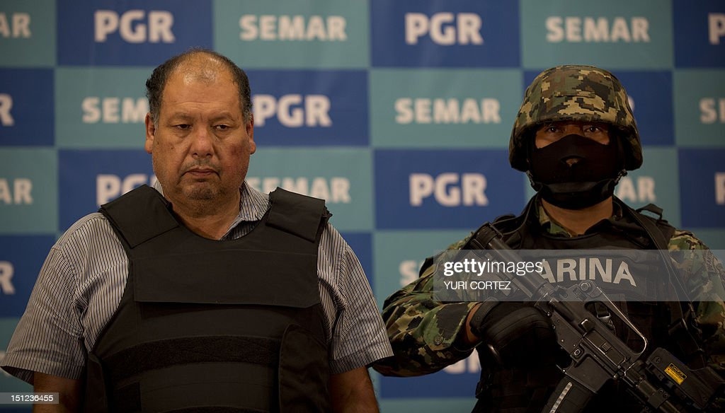 Mexican Navy members escort Mario Cardenas Guillen (L), aka 'El M-1' and alleged leader of the Gulf drug cartel, during his presentation to the press in Mexico City on September 4, 2012. According to the Navy's spokesman, Cardenas was arrested during a military operation in Altamira, Tamaulipas on September 3. AFP PHOTO/YURI CORTEZ