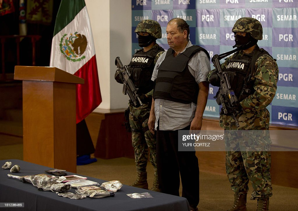 Mexican Navy members escort Mario Cardenas Guillen (C), aka 'El M-1' and alleged leader of the Gulf drug cartel, during his presentation to the press in Mexico City on September 4, 2012. According to the Navy's spokesman, Cardenas was arrested during a military operation in Altamira, Tamaulipas on September 3.