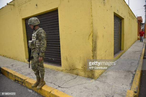 Mexican Navy members mount guard following a shootout in which eight allegedly drug traffickers were shot dead in Tlahuac Mexico City on July 20 2017...