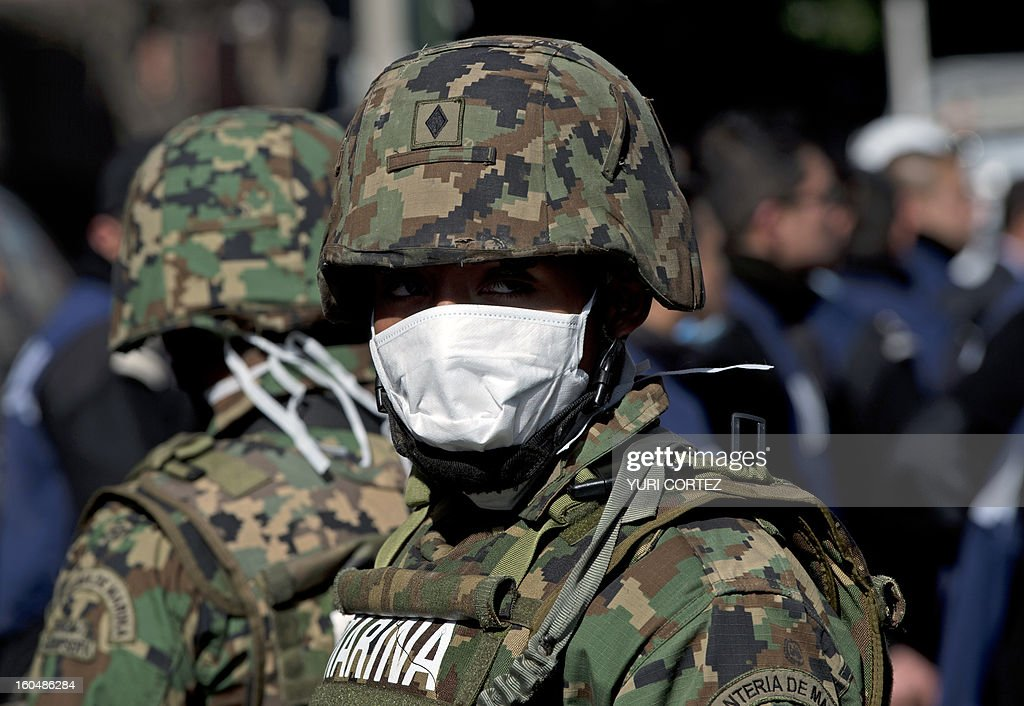 A Mexican Navy soldier stands guard at the headquarters of state-owned Mexican oil giant Pemex, where a blast took place on the eve, in Mexico City on February 1, 2013. An explosion rocked the skyscraper, leaving up to 32 dead and 121 injured. Hundreds of firefighters, police and soldiers toiled through the night after the blast ripped through an annex of the 54-floor tower also leaving concrete, computers and office furniture strewn on the ground. AFP PHOTO/Yuri CORTEZ
