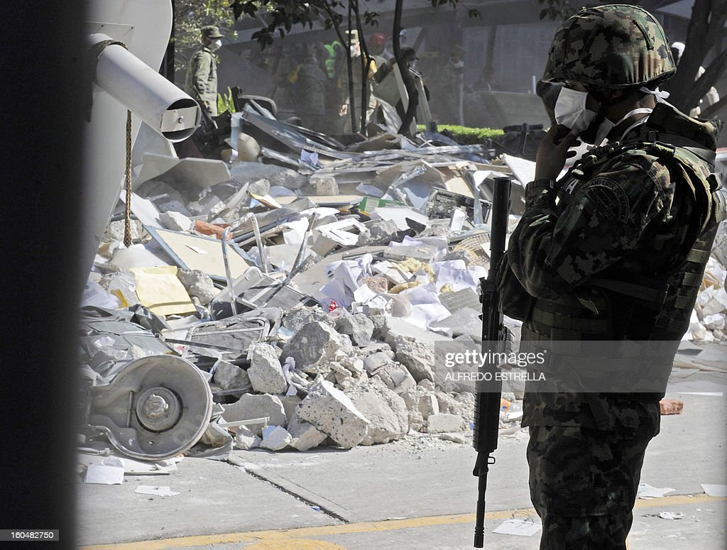 A Mexican Navy soldier stands guard inside the premises of the building that houses state-owned Mexican oil giant Pemex following a blast on the eve, in Mexico City on February 01, 2013. An explosion rocked the skyscraper, leaving up to 32 dead and 121 injured. Hundreds of firefighters, police and soldiers toiled through the night after the blast ripped through an annex of the 54-floor tower leaving concrete, computers and office furniture strewn on the ground. AFP PHOTO/Alredo Estrella